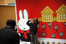 """صورة من أرشيف رويترز لرجل يلتقط صورة لصبي يقف بجوار ملصق للأرنبة """"ميفي""""."""