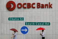 Office workers pass an Oversea-Chinese Banking Corp (OCBC) building in the central business district of Singapore January 6, 2014.  REUTERS/Edgar Su/Files