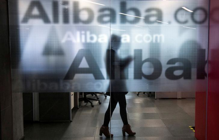 An employee is seen behind a glass wall with the logo of Alibaba at the company's headquarters on the outskirts of Hangzhou, Zhejiang province, April 23, 2014.  REUTERS/Chance Chan/File Photo