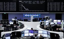 Traders work at their desks in front of the German share price index, DAX board, at the stock exchange in Frankfurt, Germany, February 17, 2017. REUTERS/staff/remote