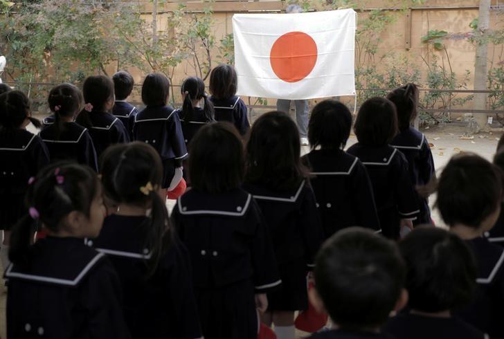 Students line up in front of Japan's national flag at the morning assembly at Tsukamoto kindergarten in Osaka, Japan, November 30, 2016. REUTERS/Ha Kwiyeon/Files