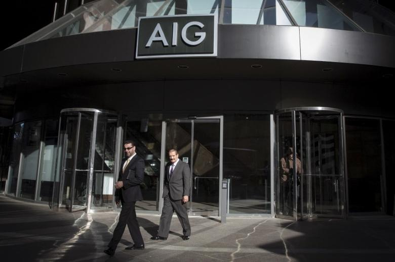 FILE PHOTO - People exit the AIG building in New York's financial district March 19, 2015. REUTERS/Brendan McDermid
