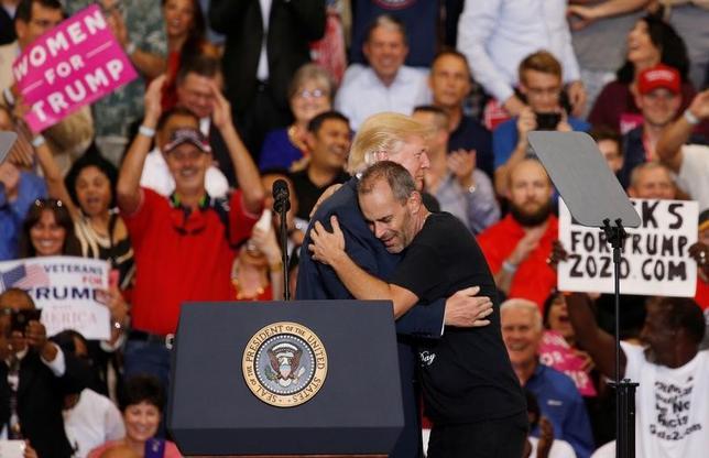 2月17日、トランプ米大統領は、就任から激動の1カ月を経て、選挙遊説という友好的で親しみやすく、活気を取り戻せそうな場所に向かおうとしている。写真は18日、フロリダ州で開いた集会で支持者の男性とハグする同大統領(2017年 ロイター/Kevin Lamarque)