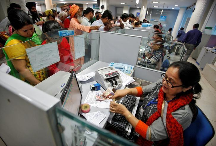 A cashier counts Indian banknotes as customers wait in queues inside a bank in Chandigarh, India, November 10, 2016. REUTERS/Ajay Verma/Files
