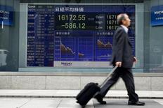 Un hombre pasa por delante de una tabla electrónica que muestra el promedio del Nikkei fuera de una correduría en Tokio, Japón, 1 de abril 2016.El índice Nikkei de la bolsa de Tokio cerró con una leve baja el jueves, luego de que los valores financieros se debilitaron por el tono cauteloso en las minutas de la última reunión de política monetaria de la Reserva Federal. REUTERS/Thomas Peter - RTSD3HP