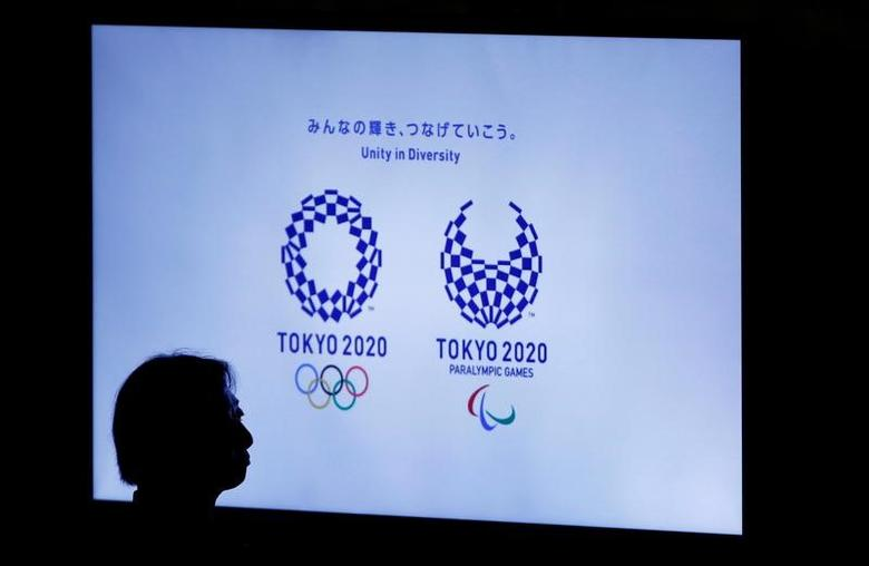 FILE PHOTO: A woman is silhouetted against a monitor showing Tokyo 2020 Olympics and Paralympics emblems during the Olympic and Paralympic flag-raising ceremony at Tokyo Metropolitan Government Building in Tokyo, Japan, September 21, 2016.  REUTERS/Toru Hanai/File Photo