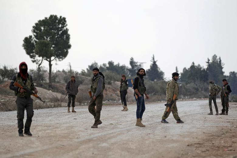 FILE PHOTO - Free Syrian Army fighters carry their weapons as they stand on the outskirts of the northern Syrian town of al-Bab, Syria February 4, 2017. REUTERS/Khalil Ashawi /File photo