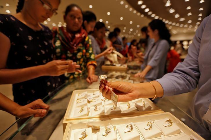 FILE PHOTO - A sales person shows a gold ring to customers at a jewellery showroom during Dhanteras, a Hindu festival associated with Lakshmi, the goddess of wealth, in Ahmedabad, India, October 28, 2016. REUTERS/Amit Dave/File photo