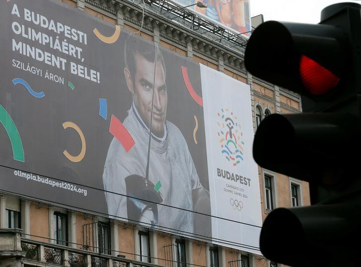 Traffic lights switch to red in front of a Hungarian pro-Olympics billboard with two-times sabre fencing Olympic champion Aron Szilagyi advertising the Games, billboard saying ''Give it all for the Budapest Olympics'' in central Budapest, Hungary, February 23, 2017.  REUTERS/Laszlo Balogh