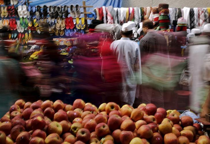 Shoppers crowd at a roadside market next to a handcart loaded with apples for sale in New Delhi, India, November 13, 2015. REUTERS/Anindito Mukherjee/File Photo