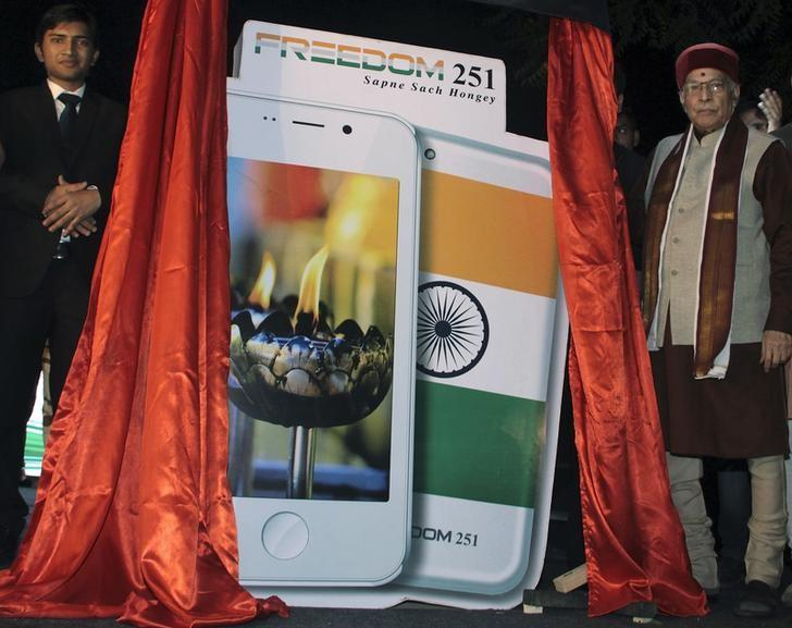 Murli Manohar Joshi (R), a senior leader of India's ruling Bharatiya Janata Party (BJP) poses next to cut-outs of Freedom 251 mobile phone during its unveiling in New Delhi, India, February 17, 2016.. REUTERS/Stringer/Files