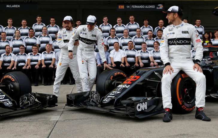 Formula One - Japanese Grand Prix - Suzuka Circuit, Japan- 7/10/16. McLaren's drivers Jenson Button of Britain, Fernando Alonso of Spain and Stoffel Vandoorne of Belgium attend the team photo session before first practice.  REUTERS/Toru Hanai