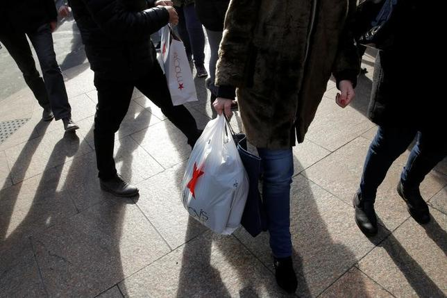 2月24日、2月の米ミシガン大消費者信頼感は96.3に低下した。写真はニューヨーク・マンハッタンで買い物袋を持って歩く人。昨年12月撮影(2017年 ロイター/Andrew Kelly)