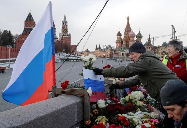 2月26日、ロシアの首都モスクワの中心部で、2年前に殺害された野党指導者ボリス・ネムツォフ元第1副首相=当時(55)=を追悼する数千人規模のデモが行われ、参加者らは事件の真相解明を訴えた。写真はネムツォフが暗殺された場所に花をささげる人々。モスクワで撮影(2017年 ロイター/Tatyana Makeyeva)