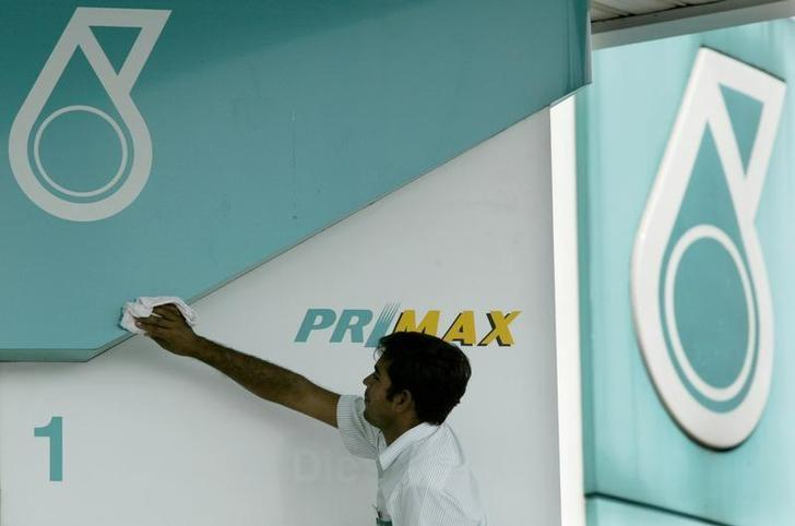 A worker cleans a Petroliam Nasional Bhd (Petronas) logo at a petrolkiosk in Kuala Lumpur on June 30, 2003.  REUTERS/Zainal Abd Halim/Files