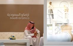 FILE PHOTO: A Saudi Aramco employee sits near the Saudi Aramco stand at the Middle East Petrotech 2016 in Manama, Bahrain, September 27, 2016.    REUTERS/Hamad I Mohammed/File Photo