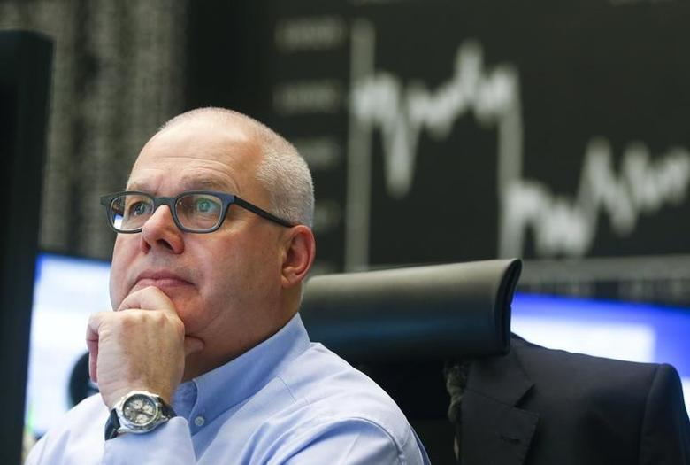 A trader is pictured at his desk in front of the German share price index DAX board at the Frankfurt stock exchange January 22, 2015.   REUTERS/Ralph Orlowski
