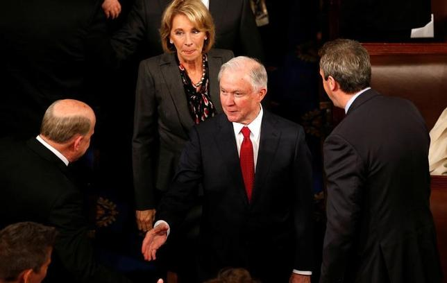 3月2日、トランプ米大統領は2日、上院の指名承認公聴会で虚偽証言を行った疑いが浮上しているセッションズ司法長官(写真中央)について、全幅の信頼を寄せているとし、支持する立場を示した。2月撮影(2017年 ロイター/Kevin Lamarque/File Photo)