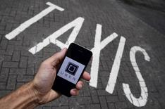 A photo illustration shows the Uber app logo displayed on a mobile telephone, as it is held up for a posed photograph in central London, Britain October 28, 2016. REUTERS/Toby Melville/Illustration/Files