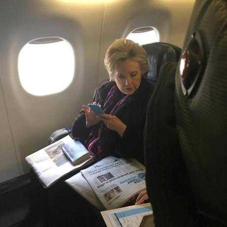 Former Democratic presidential candidate Hillary Clinton looks at a USA Today newspaper carrying an article about U.S. Vice President Mike Pence's use of personal email while in office, during her flight on American Airlines to Laguardia airport in New York City, New York, U.S. March 3, 2017.  Courtesy of Caitlin Quigley/Handout via REUTERS