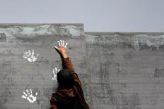 Un activista pinta un muro fronterizo entre México y Estados Unidos. Foto de archivo. REUTERS/Jose Luis Gonzalez México inició el sábado la operación de Centros de Defensoría en sus 50 consulados en Estados Unidos, a fin de ofrecer asistencia legal a inmigrantes mexicanos ante las nuevas disposiciones del Gobierno del presidente Donald Trump.