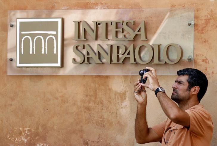 A man takes a picture in front of Intesa Sanpaolo bank in downtown Rome, Italy, July 23, 2010. REUTERS/Alessandro Bianchi/File Photo