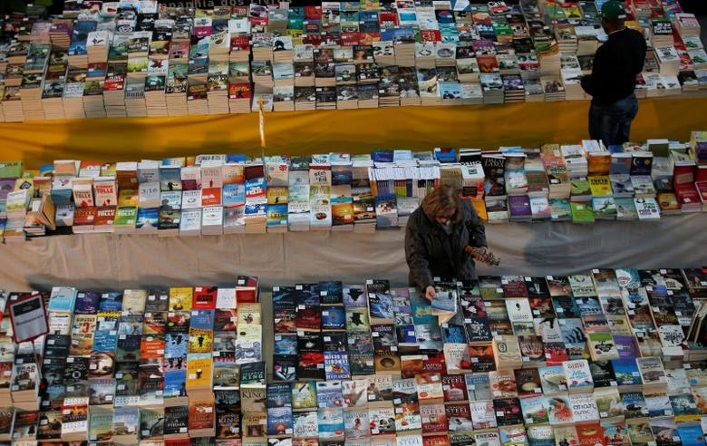 A passenger takes a book in a bookstore at Oriente train station in Lisbon, Portugal April 14, 2016. REUTERS/Rafael Marchante