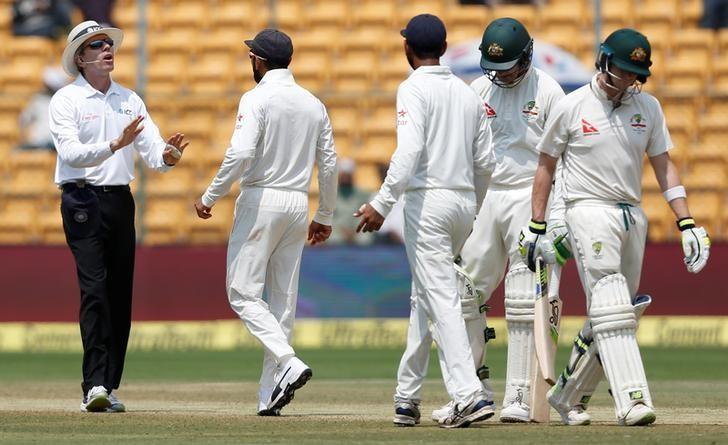 Cricket - India v Australia - Second Test cricket match - M Chinnaswamy Stadium, Bengaluru, India - 07/03/17. India's captain Virat Kohli (2nd L) speaks to the umpire as Australia's captain Steven Smith (R) walks off the ground after being dismissed. REUTERS/Danish Siddiqui
