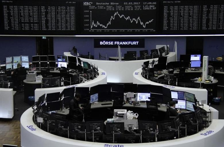 Traders work at their desks in front of the German share price index, DAX board, at the stock exchange in Frankfurt, Germany, March 3, 2017. REUTERS/Staff/Remote