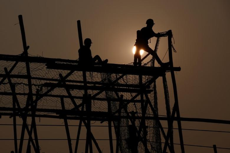 Workers build scaffolding at a construction site on a hazy day in Beijing, China, December 31, 2016.  REUTERS/Thomas Peter
