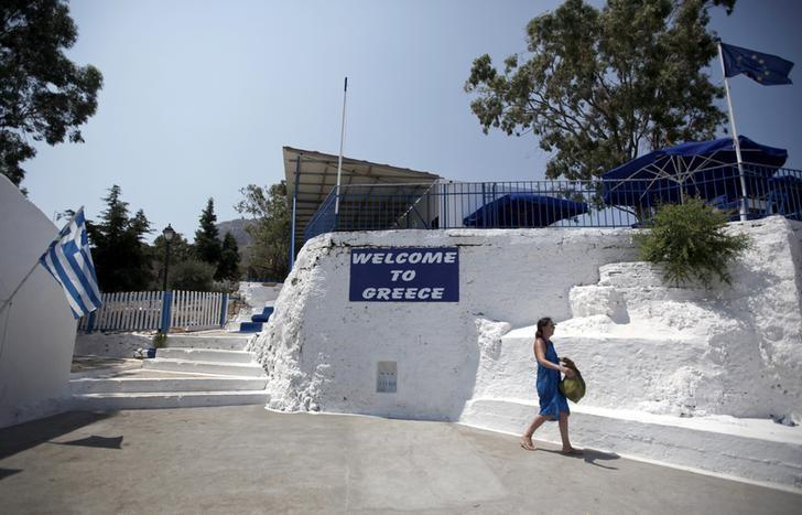 FILE PHOTO - A tourist makes her way past a Greek national flag (L) and a European Union flag on the islet of Saint George, part of the municipality of Kastellorizo, Greece's easternmost island July 30, 2015. REUTERS/Alkis Konstantinidis/File Photo