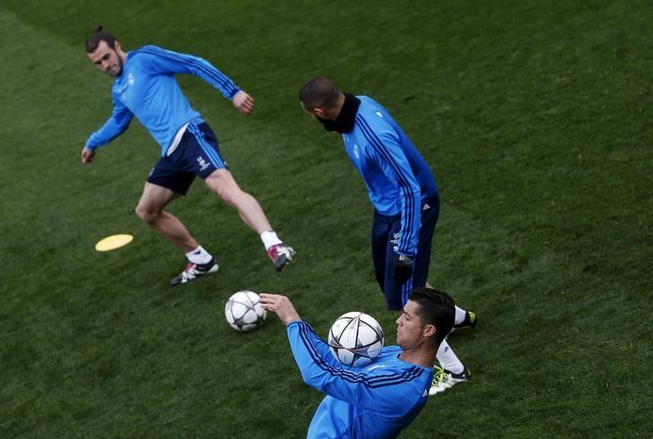 Football Soccer - Real Madrid training - Valdebebas soccer grounds, Madrid, Spain - 11/04/16 Real Madrid's Cristiano Ronaldo controls the ball next to teammates Gareth Bale (L) and Karim Benzema (R) during training on the eve of their UEFA Champions League match against VfL Wolfsburg. REUTERS/Susana Vera