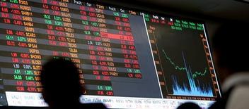 Personas observando un monitor con información bursátil en la Bolsa de Valores de Sao Paulo, mayo 9, 2016. El real brasileño retrocedió más de un 1,6 por ciento contra el dólar, con los inversores reforzando sus apuestas a que la Reserva Federal de Estados Unidos subirá las tasas de interés la próxima semana, lo que también presionó al mercado bursátil local.  REUTERS/Paulo Whitaker