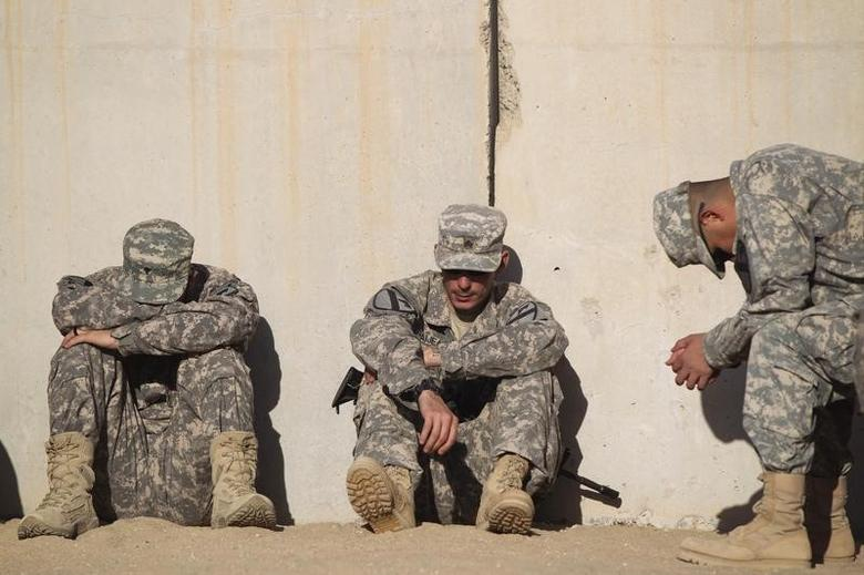 Soldiers from the 3rd Brigade Combat Team, 1st Cavalry Division rest while waiting to pack their weapons for shipment back to the United States at Camp Virginia, Kuwait December 19, 2011.   REUTERS/Lucas Jackson