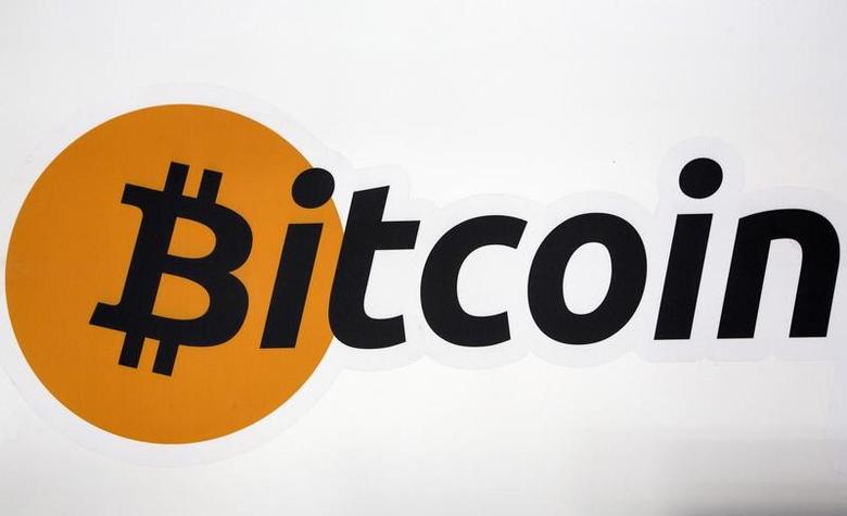 A Bitcoin logo is displayed at the Bitcoin Center New York City in New York's financial district, U.S. on July 28, 2015. REUTERS/Brendan McDermid/File Photo -