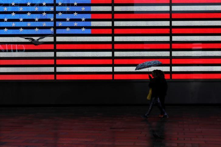 People walk by a digital U.S. flag during rain at Times Square in New York, U.S., March 7, 2017. REUTERS/Shannon Stapleton