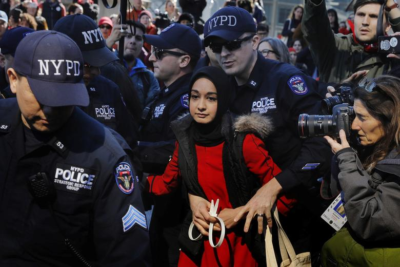 New York Police Department officers arrest a woman who was taking part in a 'Day Without a Woman' march on International Women's Day in New York. REUTERS/Lucas Jackson