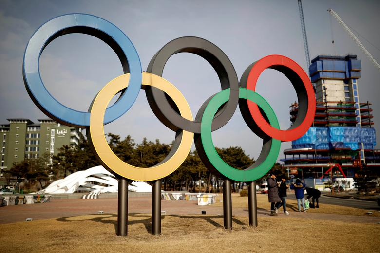 People walk past the Olympic rings in Gangneung, South Korea February 9, 2017. REUTERS/Kim Hong-Ji/File Photo