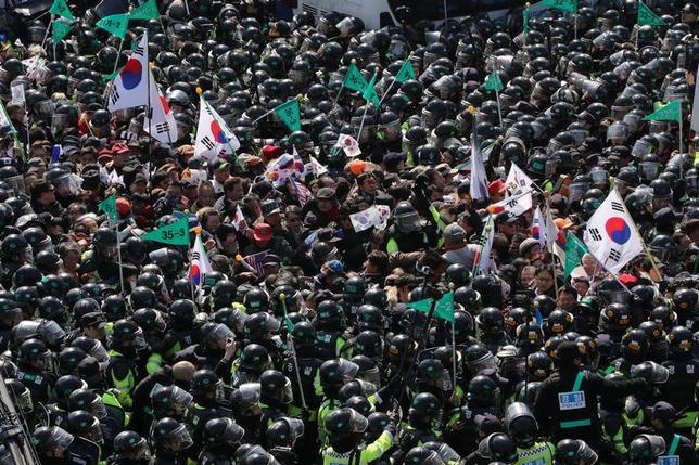 3月10日、韓国の朴槿恵大統領の罷免が決まったことを受けて行われた抗議活動で市民1人が負傷し、その後病院で死亡した。聯合ニュースが伝えた。写真はソウル市内で警察隊とぶつかる朴槿恵大統領の支持者たち。聯合ニュース提供写真(2017年 ロイター)