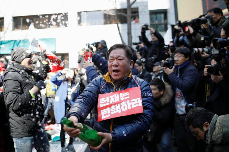 People celebrate after hearing that President Park Geun-hye's impeachment was accepted, in front of the Constitutional Court in Seoul, South Korea, March 10, 2017. REUTERS/Kim Hong-Ji