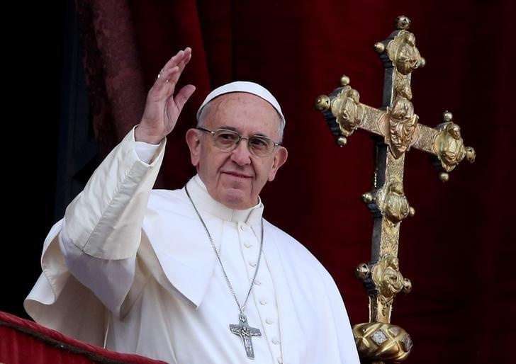 Pope Francis waves after delivering his ''Urbi et Orbi'' (to the city and the world) message from the balcony overlooking St. Peter's Square at the Vatican December 25, 2016. REUTERS/Alessandro Bianchi/File Photo
