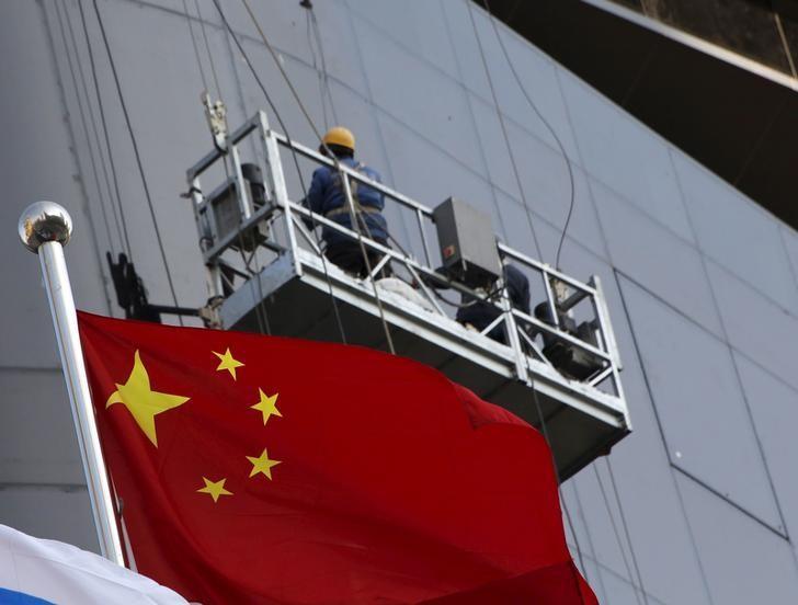 2016年1月,北京,一处建筑工地的一名工人和身后的中国国旗。REUTERS/Kim Kyung-Hoon
