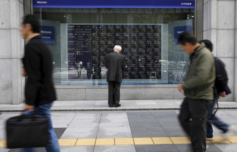 A man looks at a stock quotation board outside a brokerage in Tokyo, Japan, April 18, 2016. REUTERS/Toru Hanai/File Photo