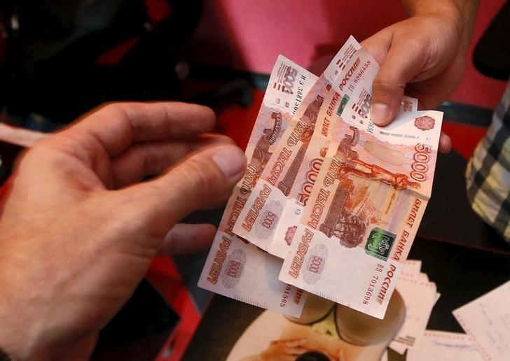 An employee (R) of a car service station takes Russian rouble banknotes from a client in the Siberian city of Krasnoyarsk, Russia, August 6, 2015.  REUTERS/Ilya Naymushin/Files