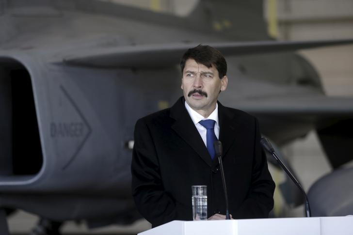 Janos Ader speaks to the media in front of a Hungarian Air Force Gripen JAS-39 fighter as he visits NATO's air policing mission over the Baltics in Siauliai Air Base, Lithuania, December 8, 2015. REUTERS/Ints Kalnins/Files