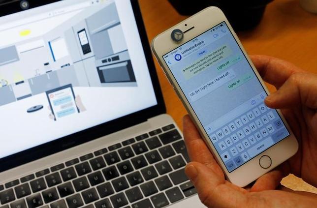 3月13日、IoT家電を備えた「スマートホーム」を制するのは音声かテキストメッセージかを巡り、ハイテク業界で議論が過熱している。写真は、シミュレーションソフトを使って家電をスマホで操作する方法を見せるユニファイドのトビー・ルッカートCEO。シンガポールで3日撮影(2017年 ロイター/Edgar Su)