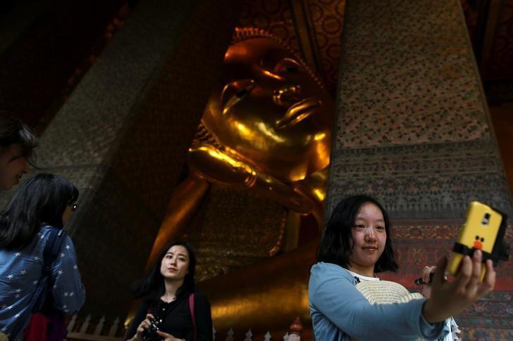Chinese tourists take selfie next to the Reclining Buddha at Wat Pho in Bangkok, Thailand, October 3, 2016. REUTERS/Athit Perawongmetha/File Photo