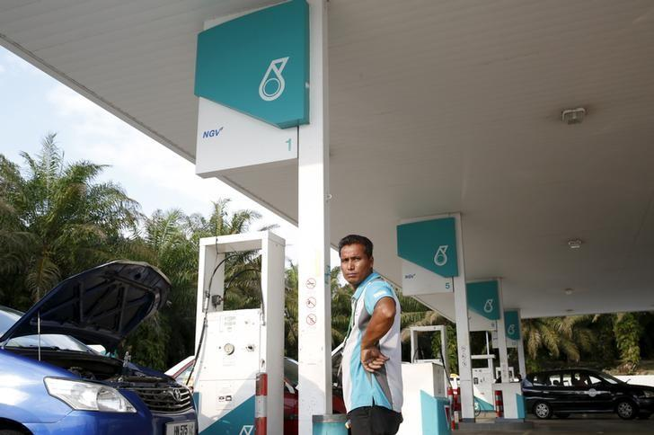 A pump attendant works at a Petronas petrol station outside Kuala Lumpur, Malaysia, March 1, 2016.  REUTERS/Olivia Harris/Files