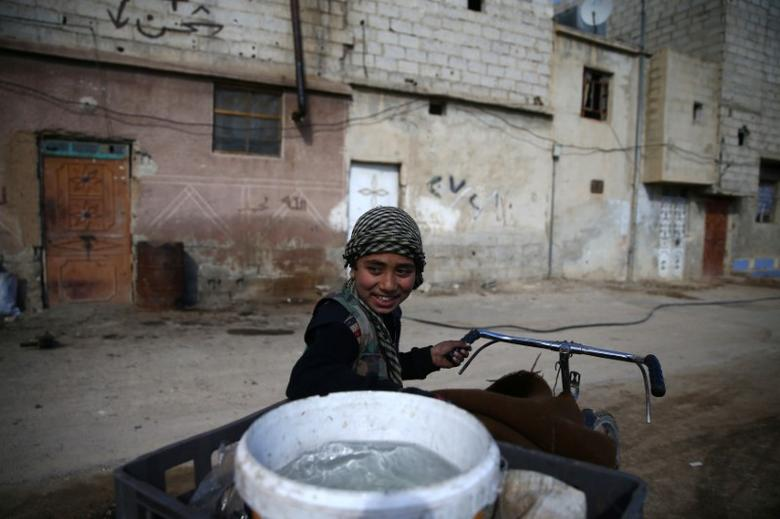 A boy transports water on a bicycle in the rebel-held besieged Douma neighbourhood of Damascus, Syria. REUTERS/Bassam Khabieh