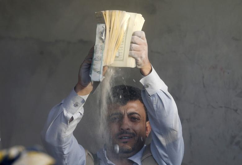 A man holds up a copy of the Koran he recovered from under the rubble of a house destroyed by a Saudi-led air strike in Yemen's capital Sanaa July 13, 2015. REUTERS/Khaled Abdullah